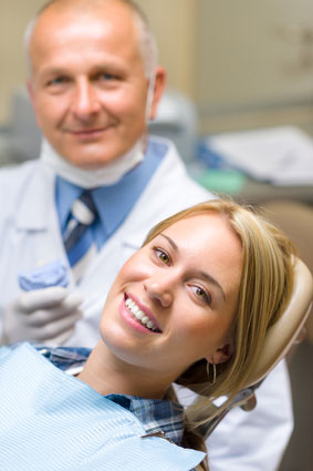 woman smiling with a dentist behind her